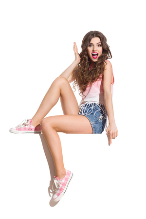 Shocked sexy woman in pink top, jeans shorts and pink sneakers sitting on the white banner and pointing down. Full length studio shot isolated on white.