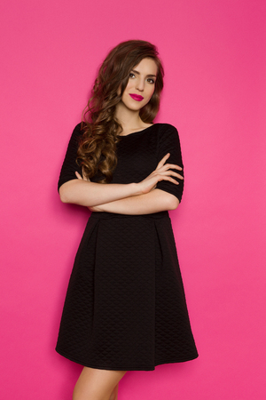 three quarter length: Cheerful elegance woman in black mini dress standing with arms crossed. Three quarter length studio shot on pink background.