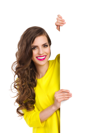 waist shot: Smiling beautiful young woman in yellow top standing behind vertical big white placard and holding it. Waist up studio shot isolated on white. Stock Photo