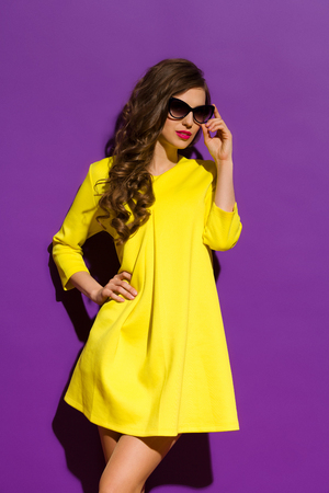 three quarter length: Beautiful girl in sunglasses posing in yellow mini dress. Three quarter length studio shot on violet background.