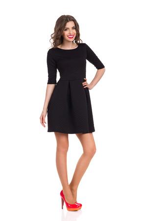 立っていると腰に手を握って黒のミニのドレスで笑顔美人完全な長さのスタジオ撮影に分離白。