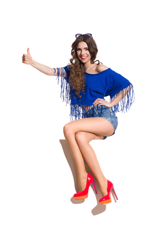 legs crossed at knee: Smiling young woman in blue top, jeans shorts and red high heels sitting at the top of white banner with legs crossed at knee and showing thumb up. Full length studio shot isolated on white. Stock Photo