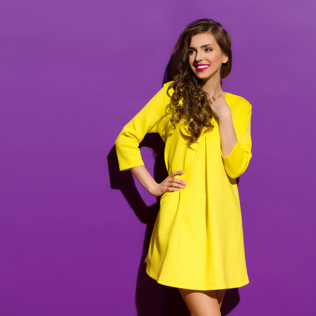 women hips: Beautiful smiling girl in yellow mini dress posing with hand on hip. Three quarter length studio shot on violet background.