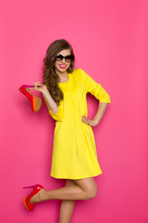 pink shoes: Happy young woman in yellow mini dress holding high heels and posing on one leg against pink background. Three quarter length studio shot.