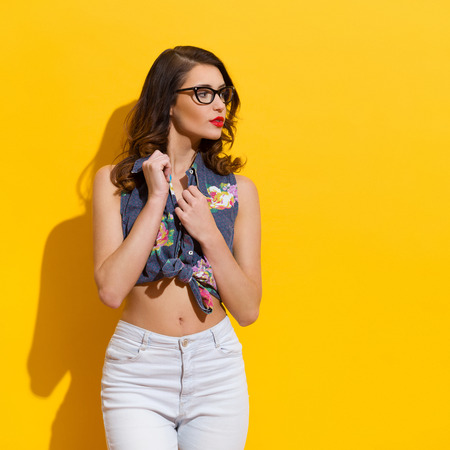 Beautiful young woman in eyeglasses looking away. Three quarter length studio shot on yellow background.