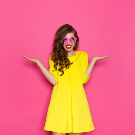 Smiling beautiful girl in yellow mini dress posing with arms outstretched and presenting something. Three quarter length studio shot on pink background.
