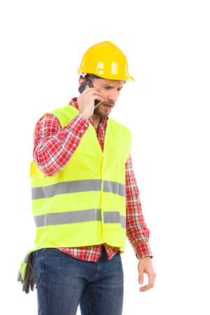 three quarter length: Disconsolate manual worker in yellow helmet and lime waistcoat talking on the cell phone. Three quarter length studio shot isolated on white.