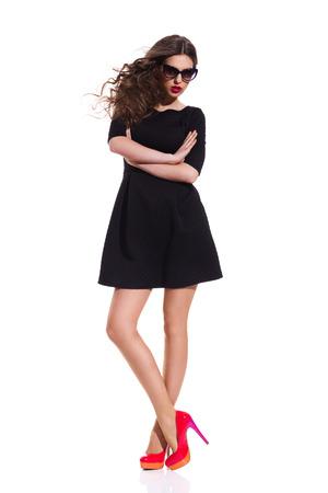 tacones rojos: Mujer hermosa en gafas de sol mini vestido negro y tacones altos rojos de pie con los brazos cruzados. Estudio de longitud completa aislado disparo en blanco.