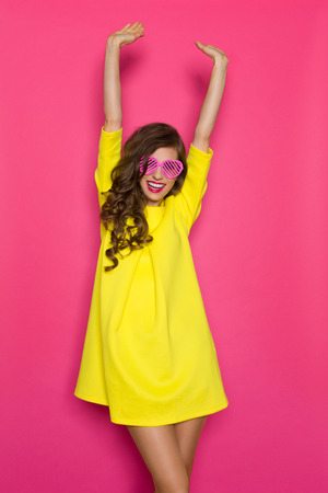Beautiful girl in yellow mini dress and pink heart shaped sunglasses posing with arms raised. Three quarter length studio shot on pink background.