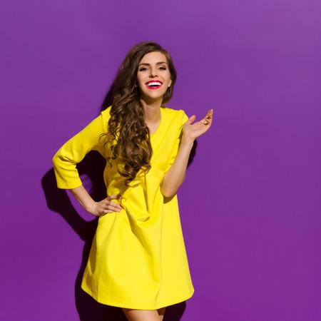 黄色のミニワン ピースでポーズ美しい幸せな女の子。4 分の 3 の長さスタジオは紫色の背景で撮影。