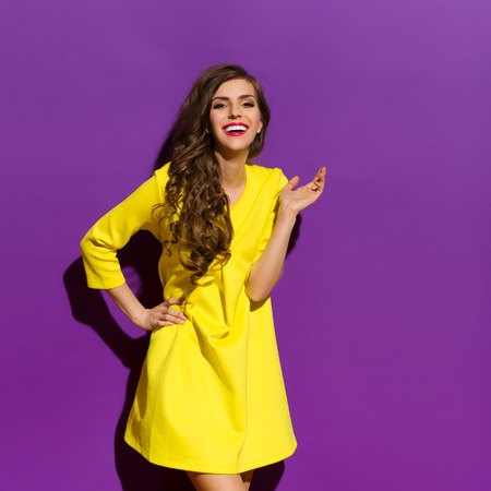 Beautiful happy girl posing in yellow mini dress. Three quarter length studio shot on violet background. Standard-Bild