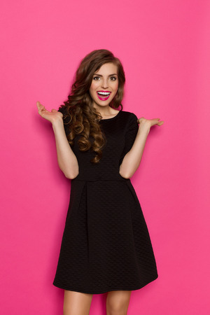 three quarter: Excited elegance woman in black mini dress standing with arms outstretched. Three quarter length studio shot on pink background.
