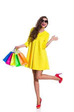 幸せなエレガンス赤いハイヒールとカラフルなショッピング バッグを押し 1 つの脚の上に立って黄色のミニのドレスの若い女性。完全な長さのスタ