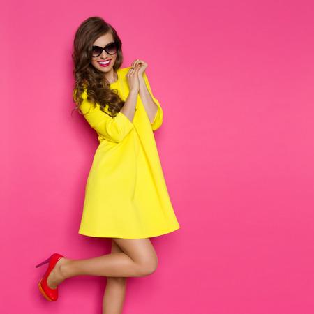 ピンク背景に片足でポーズ黄色のミニワン ピースで笑顔の美しい女性。4 分の 3 の長さのスタジオ撮影。