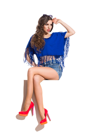 legs crossed at knee: Sexy young woman in blue top, jeans shorts and red high heels sitting on a top of the white banner with legs crossed at knee and looking away. Full length studio shot isolated on white.