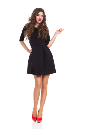 Beautiful woman in black mini dress standing and pointing. Full length studio shot isolated on white.