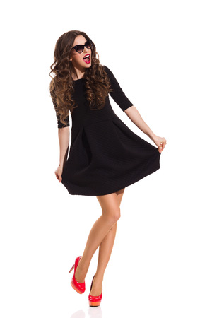 Neat woman in sunglasses, black mini dress and red high heels posing on one leg and shouting. Full length studio shot isolated on white.