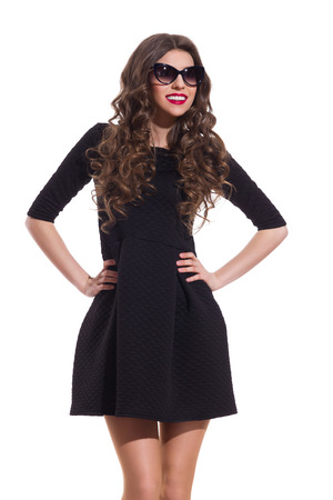 three quarter length: Beautiful young woman in sunglasses and black mini dress posing with hands on hip. Three quarter length studio shot isolated on white. Stock Photo