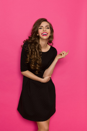 pink black: Smiling elegance woman in classic black mini dress. Three quarter length studio shot on pink background. Foto de archivo