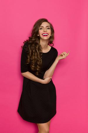 rosa negra: Sonriente mujer de elegancia en mini vestido negro cl�sico. Tres cuartos de longitud estudio tirado en el fondo de color rosa.