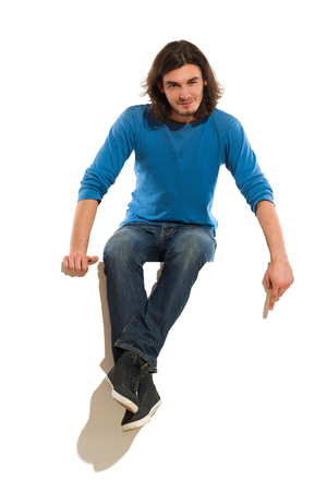 Young man sitting on a banner and pointing down. Full length studio shot isolated on white.