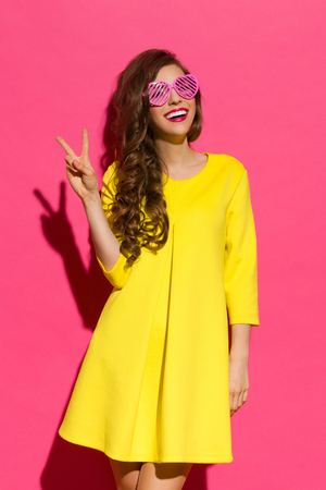 Beautiful girl in yellow mini dress and pink heart shaped sunglasses posing with peace hand sign. Three quarter length studio shot on pink background.