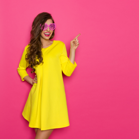 Smiling beautiful girl in pink sunglasses and yellow mini dress posing against pink background and pointing. Three quarter length studio shot. Фото со стока
