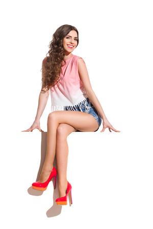 Sonriente mujer atractiva en tapa rosada, pantalones vaqueros y zapatos de tacón rojo sentado en la parte superior de la bandera blanca. Estudio de longitud completa aislado disparo en blanco.
