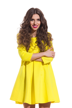 three quarter: Smiling young woman with long curly hair posing with arms crossed in yellow mini dress. Three quarter length studio shot isolated on white. Stock Photo