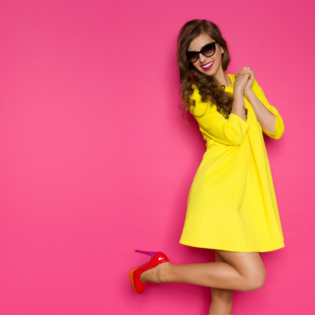 tacones rojos: Emocionado chica en vestido mini amarillo posando en una pierna contra el fondo de color rosa. Tres cuartos de longitud de tiro del estudio. Foto de archivo