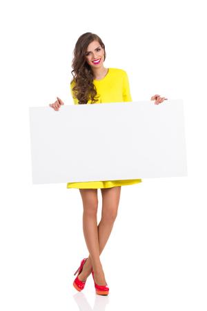 modelos posando: Sonriente mujer joven en vestido amarillo y rojo tacones altos de pie y la celebraci�n de un gran cartel blanco. Estudio de longitud completa aislado disparo en blanco. Foto de archivo