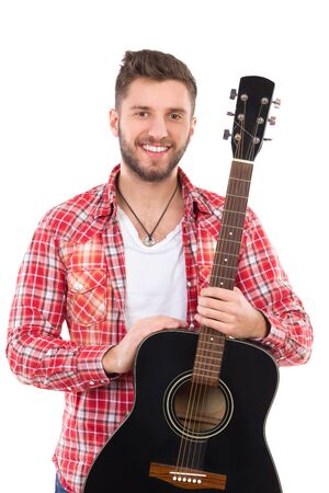 waist shot: Smiling male guitarist in red lumberjack shirt posing with a black acoustic guitar. Waist up studio shot isolated on white. Stock Photo