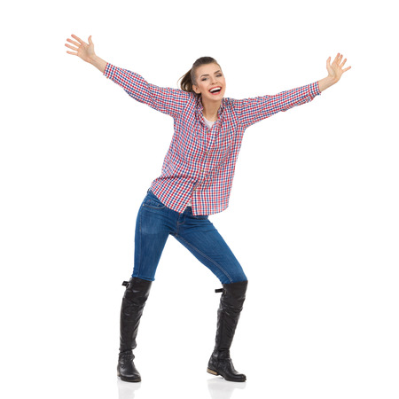 lumberjack shirt: Young woman in jeans, black boots and lumberjack shirt standing with arms outstretched and shouting. Full length studio shot isolated on white. Stock Photo