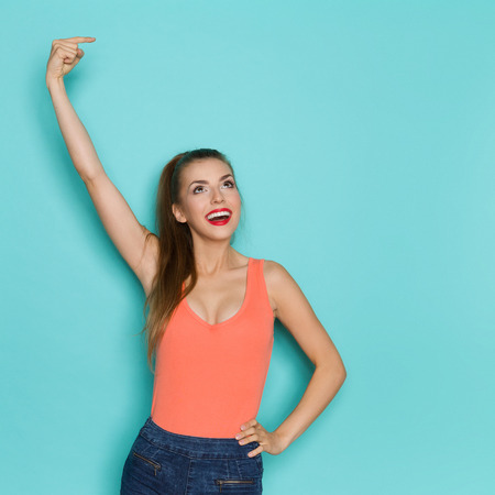 Happy beautiful young woman in orange shirt pointing over her head at copy space and looking up. Waist up studio shot on teal background.