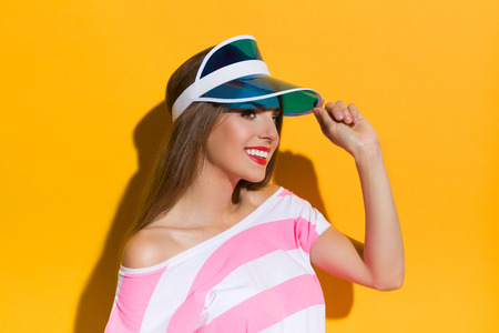 visor: Smiling young woman in pink stripped shirt holding sun visor cap and looking away. Studio portrait on yellow background. Stock Photo