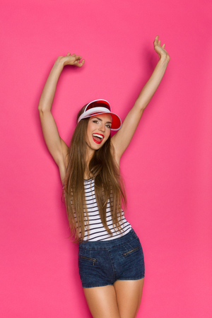visor: Young beautiful woman in jeans shorts, striped shirt and red sun visor posing with arms raised and shouting. Three quarter length studio shot on pink background.