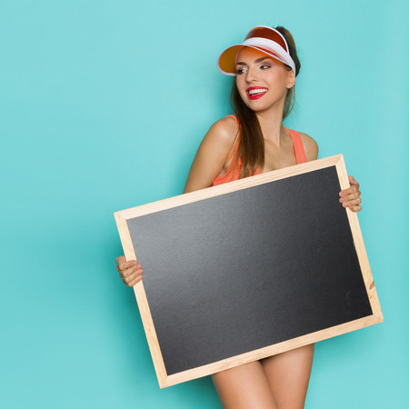 visor: Smiling young woman in orange shirt and sun visor holding blackboard and looking away.Three quarter length studio shot on turquoise background. Stock Photo