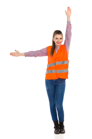 horizontally: Young woman in orange reflective vest, lumberjack shirt, jeans, black boots, standing with arms outstretched, holding one hand horizontally and the other verticallyl. Full length studio shot isolated on white. Stock Photo
