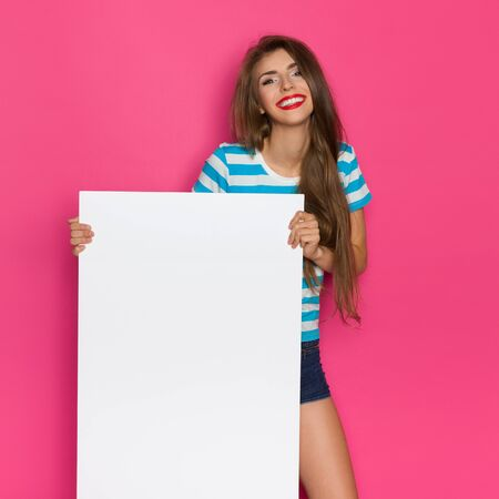 three quarter: Happy beautiful young woman in striped shirt posing with white poster. Three quarter length studio shot on pink background. Stock Photo