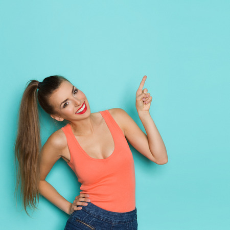 ponytail: Smiling beautiful young woman with ponytail pointing up at copy space. Waist up studio shot on teal background. Stock Photo