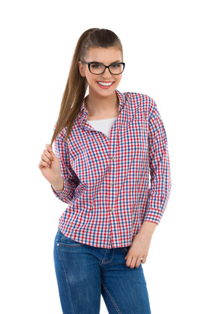 lumberjack shirt: Smiling young woman in glasses, lumberjack shirt and jeans posing and holding her ponytail in hand. Three quarter length studio shot isolated on white. Stock Photo