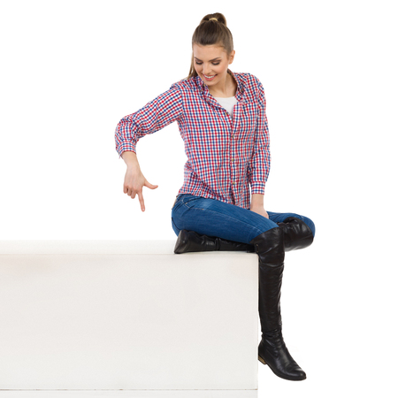 lumberjack shirt: Casual young woman in lumberjack shirt, jeans and black boots sitting on a top of white box and looking down and pointing. Side view. Full length studio shot isolated on white.