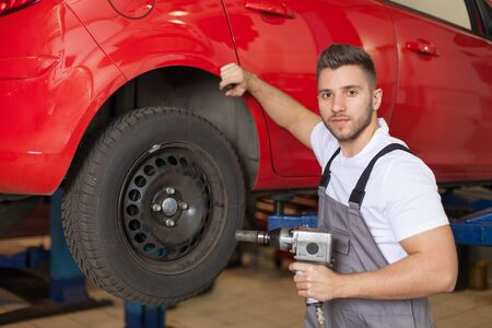 impact wrench: Mechanic in workwear waiting with an impact wrench against red car in workshop Stock Photo