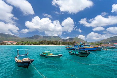 con dao: Vietnamese fishing boats on a tropical Con Dao Island. View from the pier in the direction of a beach with white sand.