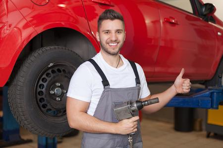impact wrench: Smiling man in workwear posing in workshop holding an impact wrench against and showing thumb up