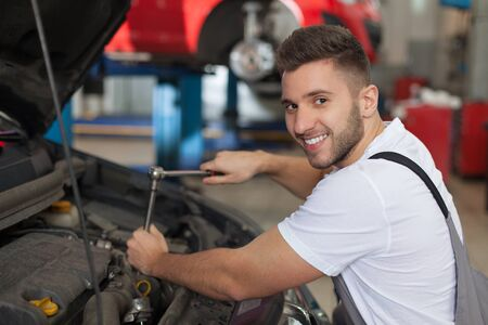 Man in an auto repair shop fixing an engine with a ratchet wrench