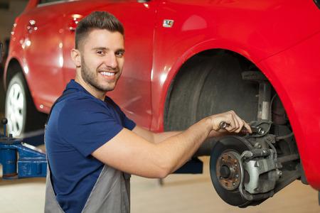 自動車整備士店でブレーキ車を修理メカニックを笑顔