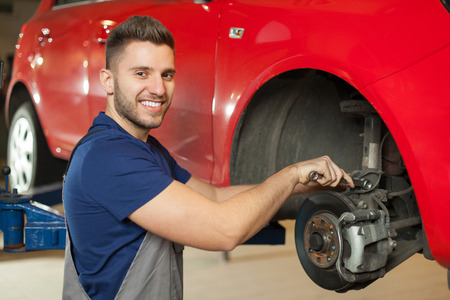 Smiling mechanic repairing a car brakes in auto mechanic shop Banco de Imagens