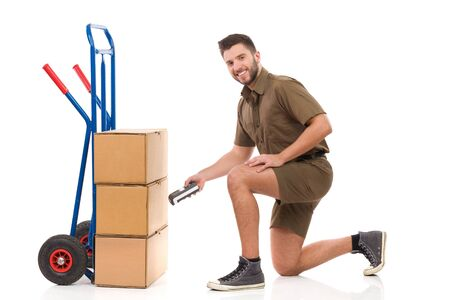 man kneeling: Smiling delivery man kneeling close to carton box and holding digital equipment. Full length studio shot isolated on white.