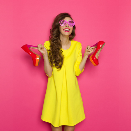 Laughing young woman in yellow mini dress and pink sunglasses holding a red high heels. Three quarter length studio on pink background.